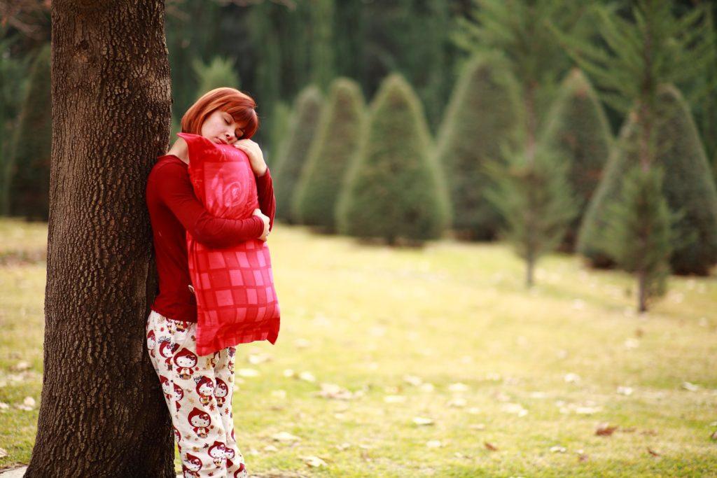 utrujena ženska spi ob drevesu