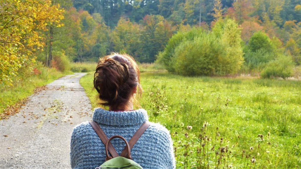 ženska zamišljena v naravi na sprehodu
